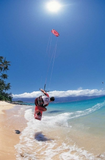Kitesurfer skimming sandy beach [photo] - Kitesurfing