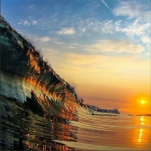 Stunning photo of the sunset reflecting of a glassy wave - Surfing