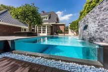 Visually stunning infinity edge pool with glass wall - Swimming Pools