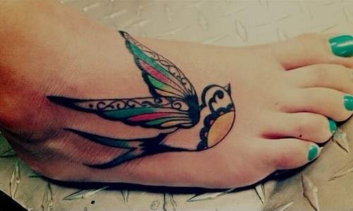 Colorful bird tattoo on foot