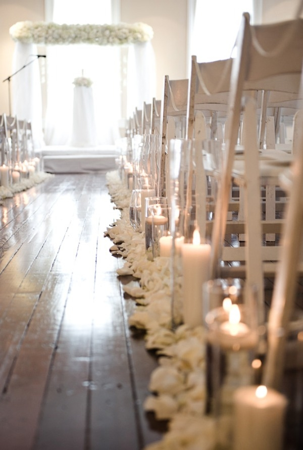 white flowers, and candles line the main isle